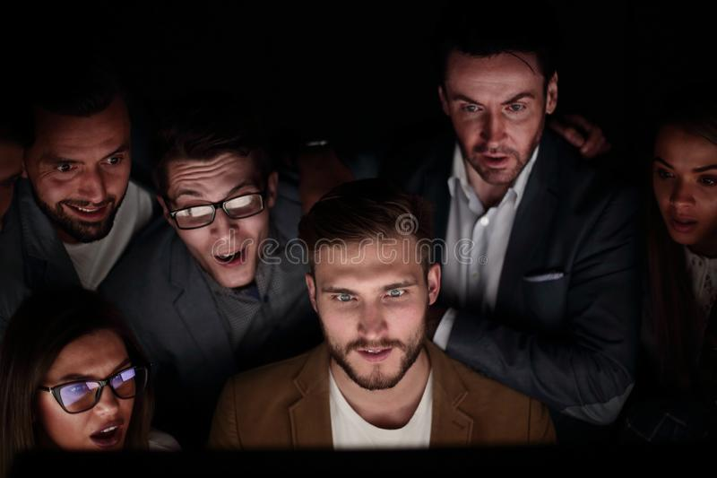 close upp programmeraren och hans kollegor arbetar sent royaltyfri bild