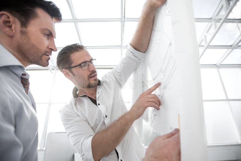 close upp två arkitekter som står nära den faktiska skärmen royaltyfri bild