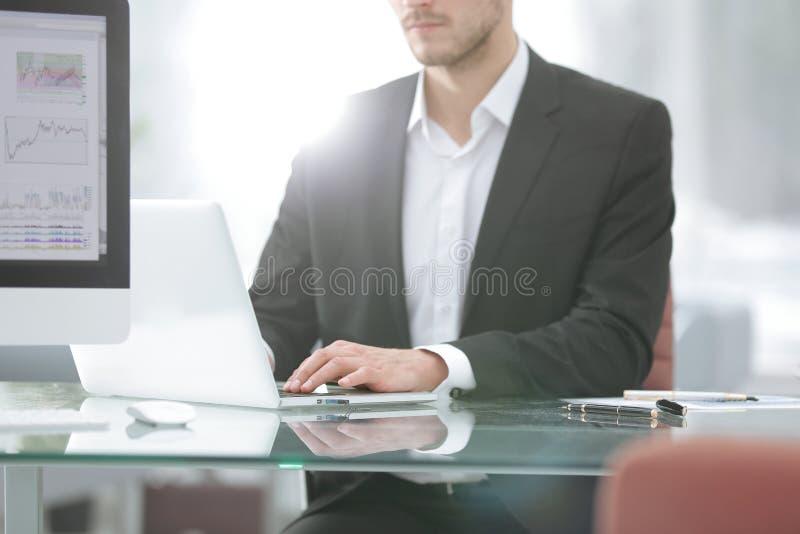 close upp Ung man som arbetar med en bärbar dator, en mänsklig hand på anteckningsboken royaltyfria bilder