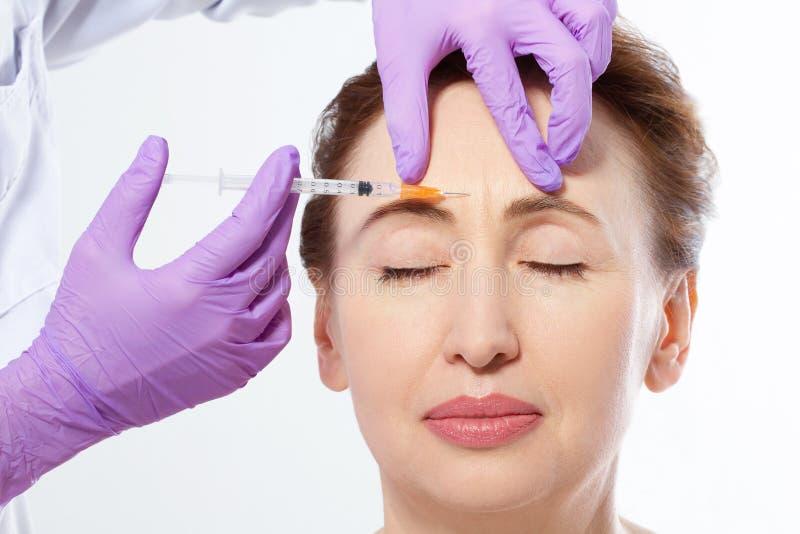 Close-upportret dat van een mooie middenleeftijd vrouw en artsenhanden botox injectie maakt die op witte achtergrond wordt geïsol stock foto's