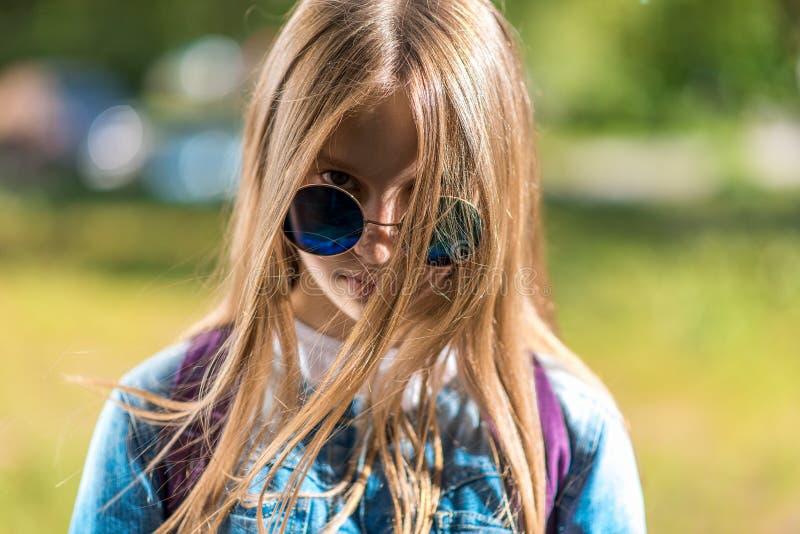 Close-upportret, de tiener van het meisjesschoolmeisje De zomer in aard Lange haar en zonnebril Onderzoekt emotioneel kader stock afbeeldingen