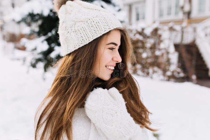 Close-upportret die jonge vrouw in witte wollen handschoenen charmeren, gebreide hoed die, lang donkerbruin haar van de koude win stock fotografie