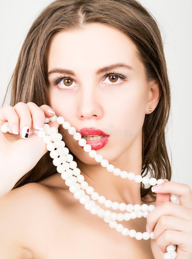 Close-upportret die van een mooi meisje met rode lippen, een parelhalsband houden open de mond, parels raakt haar lippen Rood stock fotografie