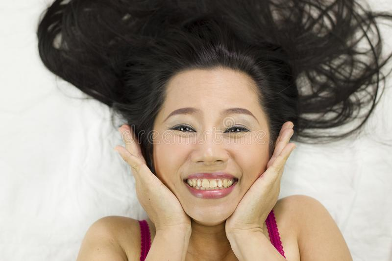 Close-upportret die van gelukkige Aziatische vrouwen op grond met zwart lang haar liggen acterenglimlach, pret stock fotografie