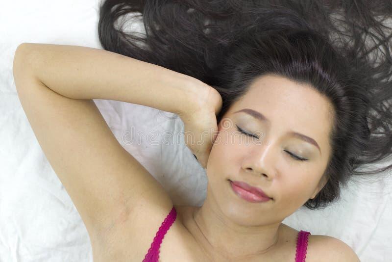 Close-upportret die van gelukkige Aziatische vrouwen op grond met zwart lang haar liggen acterenglimlach, pret stock foto