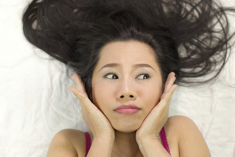 Close-upportret die van humeurige Aziatische vrouwen op grond met zwart lang haar liggen verstoord acteren, ongelukkig royalty-vrije stock afbeelding