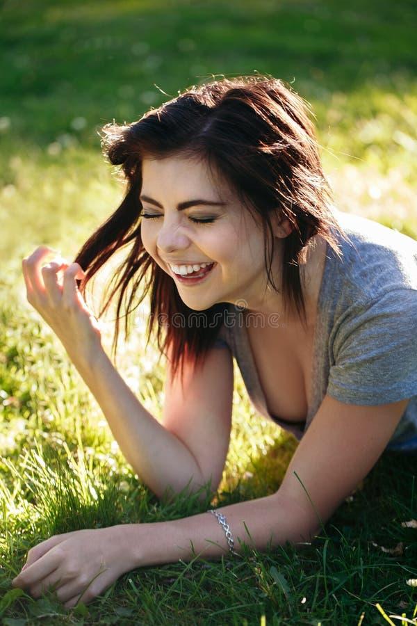 Close-upportret die van mooie glimlachende jonge Kaukasische vrouw met rood zwart haar, op gras in openlucht liggen, het lachen royalty-vrije stock foto
