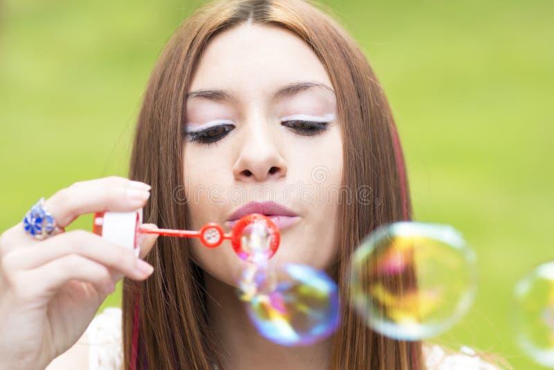 Close-upportret die van mooie vrouw kleurrijke zeep opblazen bubb stock afbeeldingen