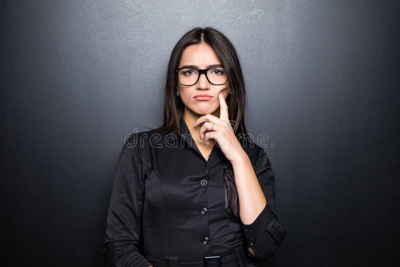 Close-upportret, sceptische, ernstige hogere jonge vrouw die verdacht, afkeuring op gezicht geïsoleerde zwarte achtergrond kijken stock afbeeldingen