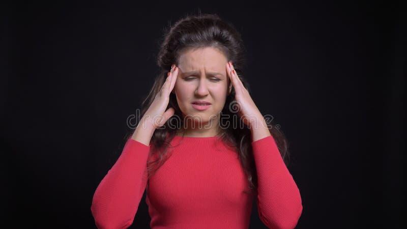Close-upportret van aantrekkelijk Kaukasisch wijfje die op middelbare leeftijd een hoofdpijn voor de camera met achtergrond hebbe stock foto