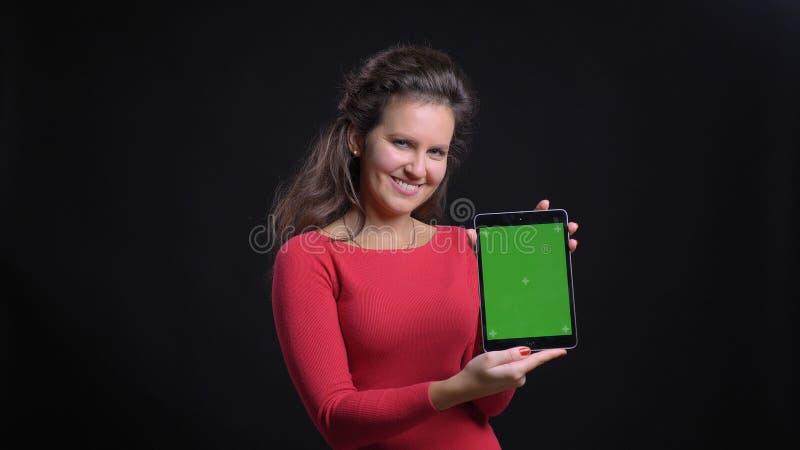 Close-upportret van aantrekkelijke Kaukasisch op middelbare leeftijd gebruikend de tablet en tonend het groene chromascherm aan c stock foto's