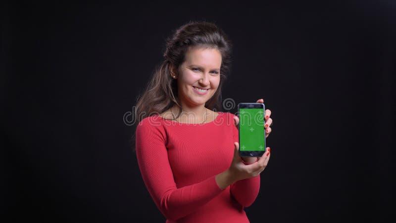 Close-upportret van aantrekkelijke Kaukasisch op middelbare leeftijd gebruikend de tablet en tonend het groene scherm aan camera  stock foto