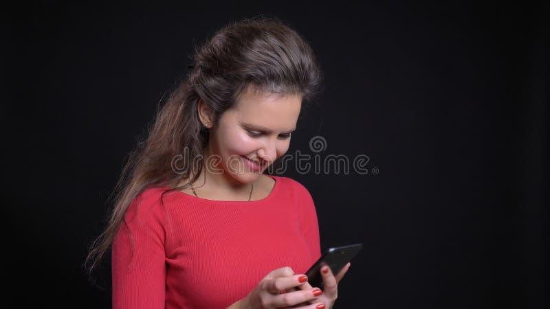 Close-upportret van aantrekkelijke Kaukasisch op middelbare leeftijd gebruikend de telefoon en cheerfully glimlachend voor de cam stock afbeelding
