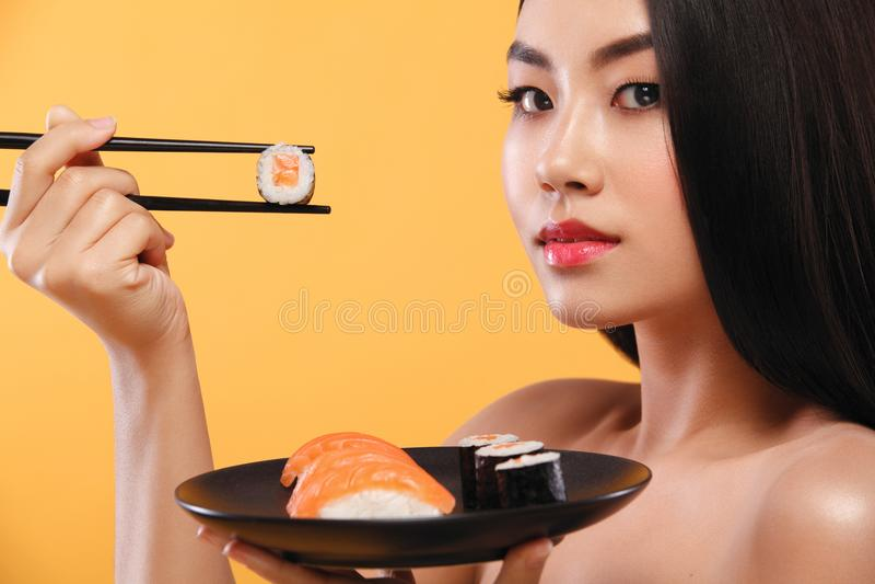 Close-upportret van Aziatische vrouw die sushi en broodjes op een gele achtergrond eten stock afbeeldingen