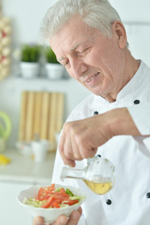 Close-upportret van bejaarde mannelijke chef-kok gietende olie in salade stock fotografie