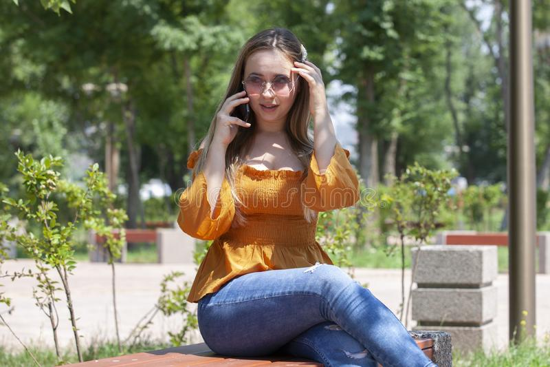 Close-upportret van betoverend meisje in glazen die op telefoon spreken Openluchtportret een blonde jonge vrouw die door haar sma stock foto's