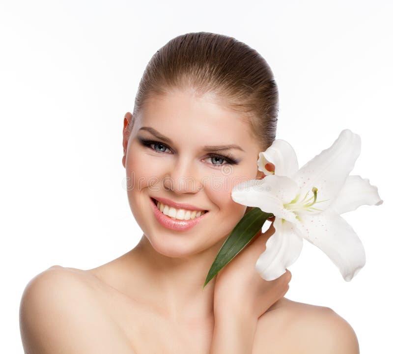 Close-upportret van blij, glimlachend Kaukasisch meisje met witte bloem in haar hand stock fotografie