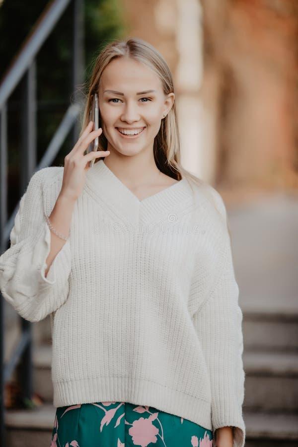 Close-upportret van blondemeisje het spreken op telefoon op straat met schoonheidsglimlach stock afbeeldingen
