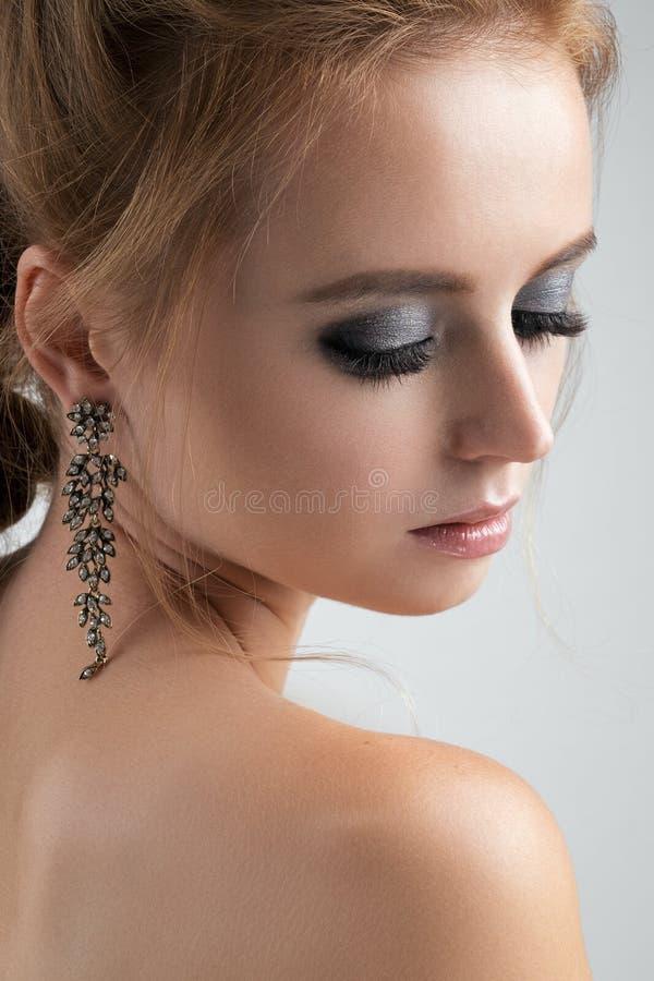 Close-upportret van blonden met lange oorringen met gesloten ogen en zilverachtige oogschaduw stock fotografie
