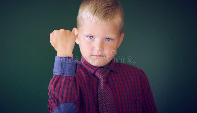 Close-upportret van boze Kaukasische jongen die vuist tonen, eisend rechtvaardigheid, zijn rechten De jongen isoleerde groene muu royalty-vrije stock foto's