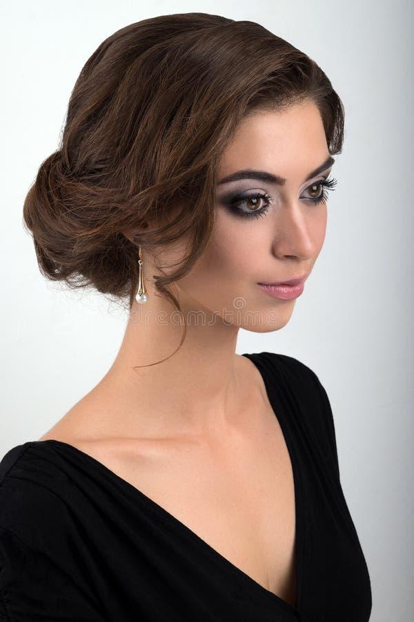Close-upportret van brunette met avondmake-up en verzameld haar in een zwarte kledings bevindende helft-draai op een lichte achte royalty-vrije stock fotografie