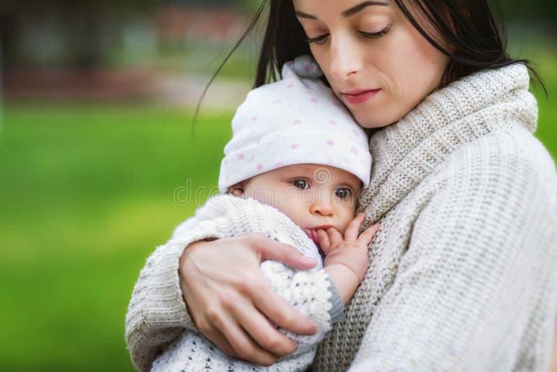 Close-upportret van de baby van de mammaholding in openlucht bij parkachtergrond Concept gelukkige familie royalty-vrije stock foto
