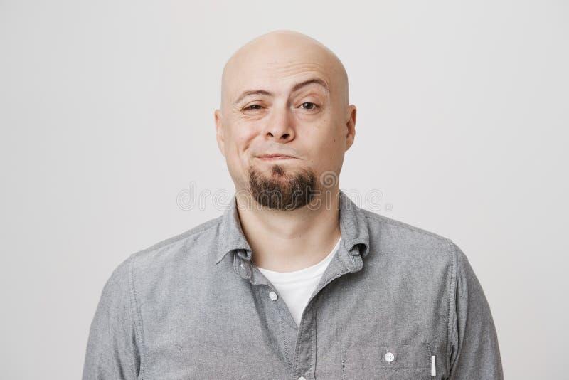Close-upportret van de blije aantrekkelijke kale gebaarde mens, verdacht of aarzeling die over iets, status kijken stock foto