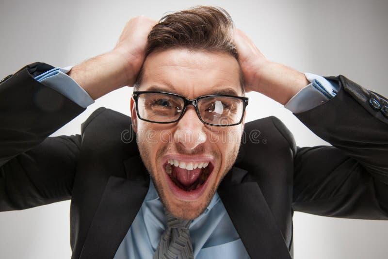 Close-upportret van de boze, gefrustreerde mens, die zijn haar uit trekken stock afbeelding