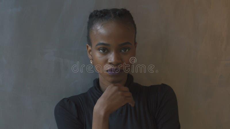 Close-upportret van de ernstige Afro-Amerikaanse vrouw met purpere lippenstift en vlechten die in camera grijs bekijken stock afbeelding