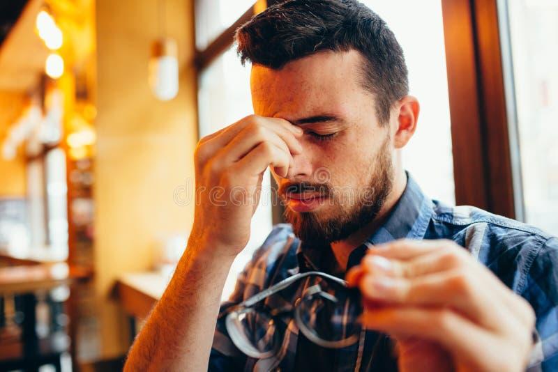 Close-upportret van de jonge mens met glazen, die zichtproblemen heeft stock foto