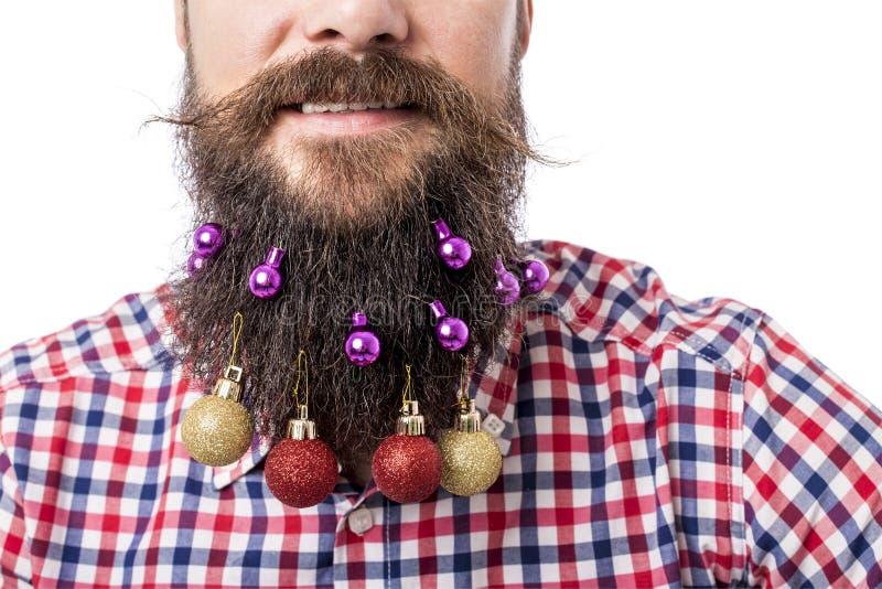 Close-upportret van de mens met decoratieballen in zijn baard stock afbeelding