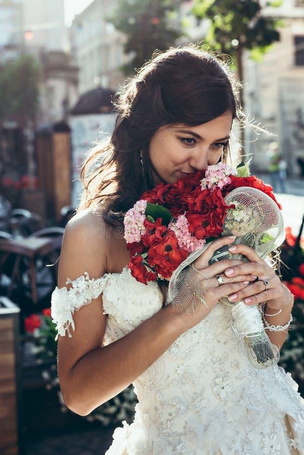 Close-upportret van de mooie donkerbruine bruid die het huwelijksboeket van rode en roze bloemen ruiken stock afbeelding
