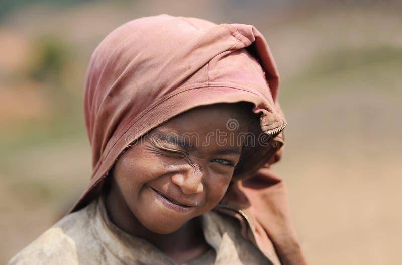 Close-upportret van de niet geïdentificeerde glimlachende jongen van Madagascar met een grimas op een gezicht stock foto