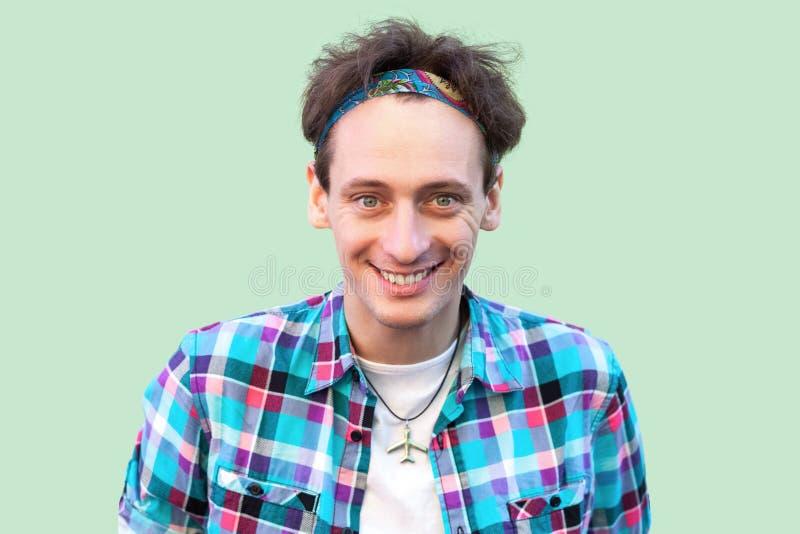 Close-upportret van de opgewekte jonge mens in toevallig blauw geruit overhemd en hoofdband die en zich camera met geluk bevinden stock afbeelding