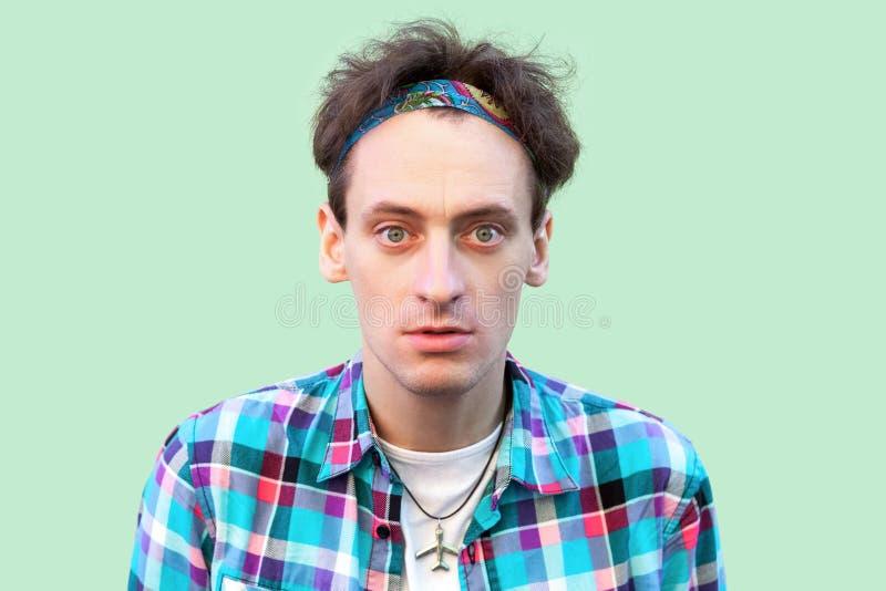 Close-upportret van de verwarde jonge mens in toevallig blauw geruit overhemd en hoofdband die en zich camera met geschokt bevind stock foto