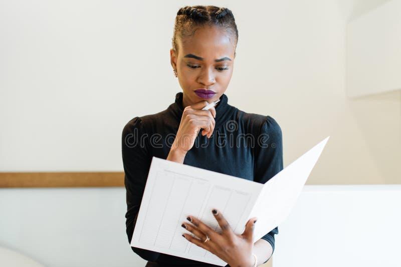 Close-upportret van denkende succesvolle Afrikaanse of zwarte Amerikaanse bedrijfsvrouw die een grote witte dossier en een pen ho royalty-vrije stock fotografie