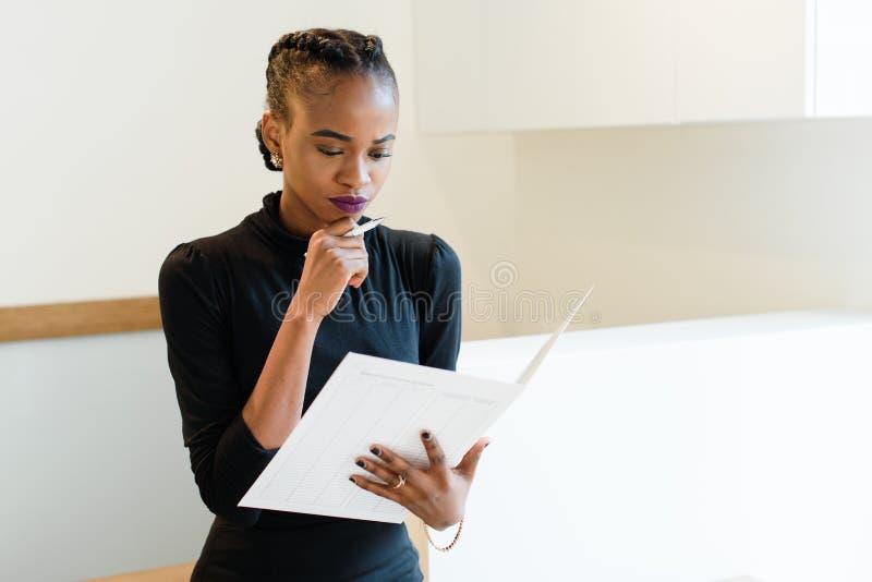 Close-upportret van denkende succesvolle Afrikaanse of zwarte Amerikaanse bedrijfsvrouw die een grote witte dossier en een pen ho stock foto's