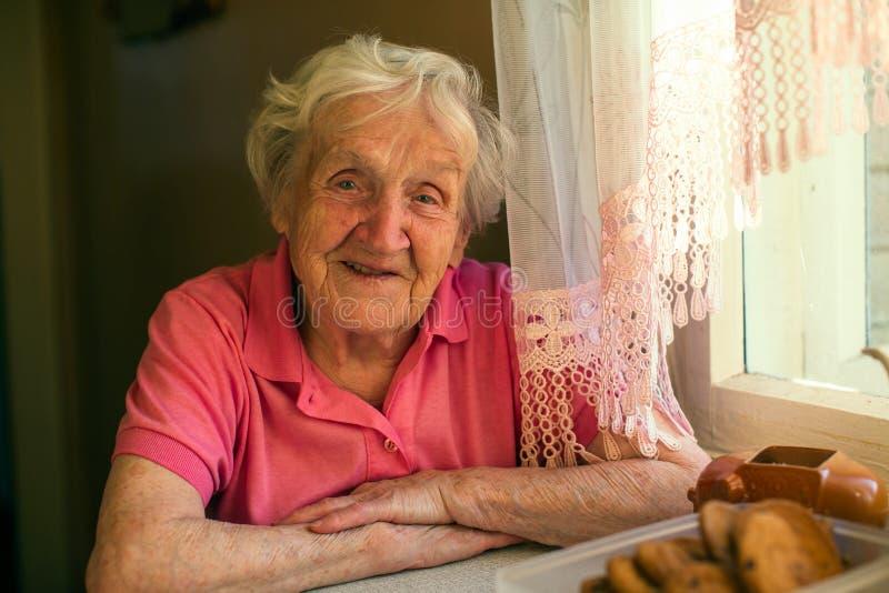 Close-upportret van een bejaarde gelukkige vrouw in haar huis royalty-vrije stock afbeeldingen
