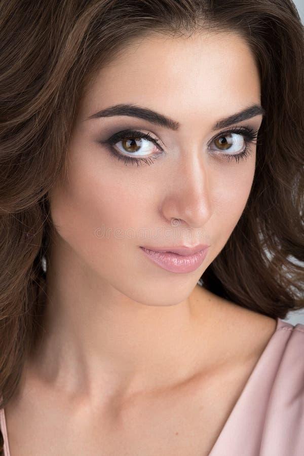 Close-upportret van een brunette met avondmake-up in een lichtrose kleding stock fotografie