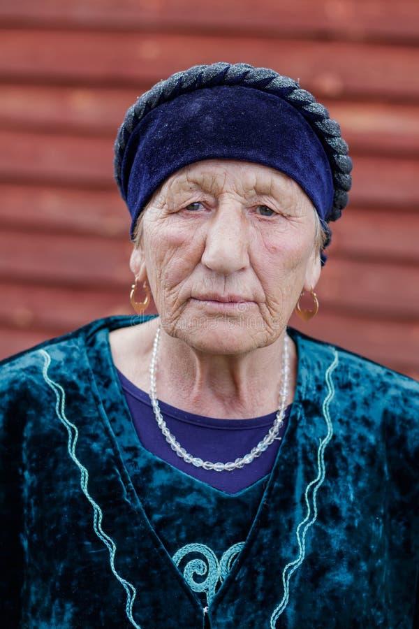 Close-upportret van een dorpsbejaarde in een nationaal kostuum stock fotografie