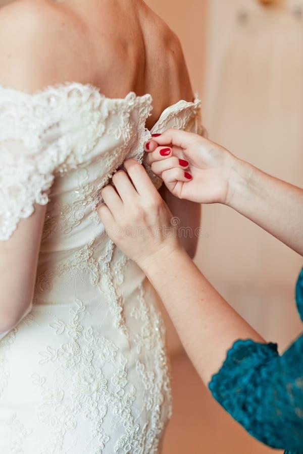 Close-upportret van een eerste bruidsmeisje die de bruid helpen stock afbeelding