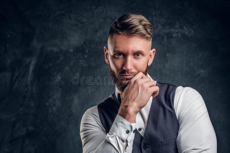 Close-upportret van een elegant geklede jonge mens met modieuze baard en haarholdingshand op een kin en het bekijken a stock afbeelding