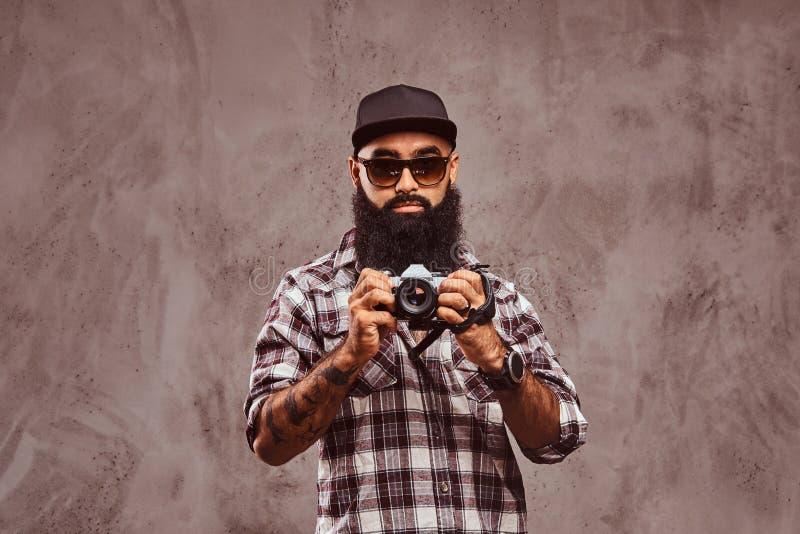 Close-upportret van een gebaard Arabisch mannetje geruite overhemdszonnebril dragen en GLB die een camera houden stock foto's