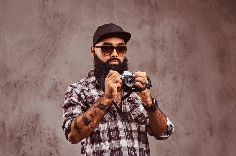 Close-upportret van een gebaard Arabisch mannetje geruite overhemdszonnebril dragen en GLB die een camera houden royalty-vrije stock afbeelding