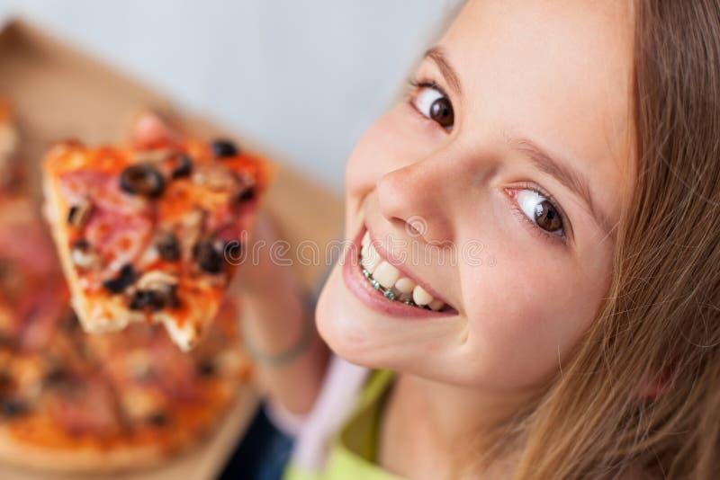 Close-upportret van een gelukkig jong tienermeisje die een plak o eten stock fotografie