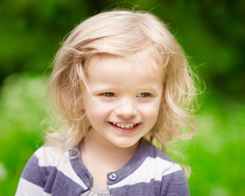 Close-upportret van een glimlachend blondemeisje met krullend haar stock foto's