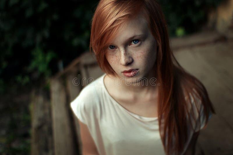 Close-upportret van een jong roodharig meisje die met sproeten en blauwe ogen de camera omhoog onderzoeken stock foto's