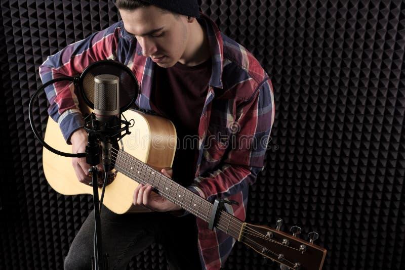 Close-upportret van een jonge kerel in een plaidoverhemd die een gitaar voor een microfoon spelen tegen een grijze muur stock foto