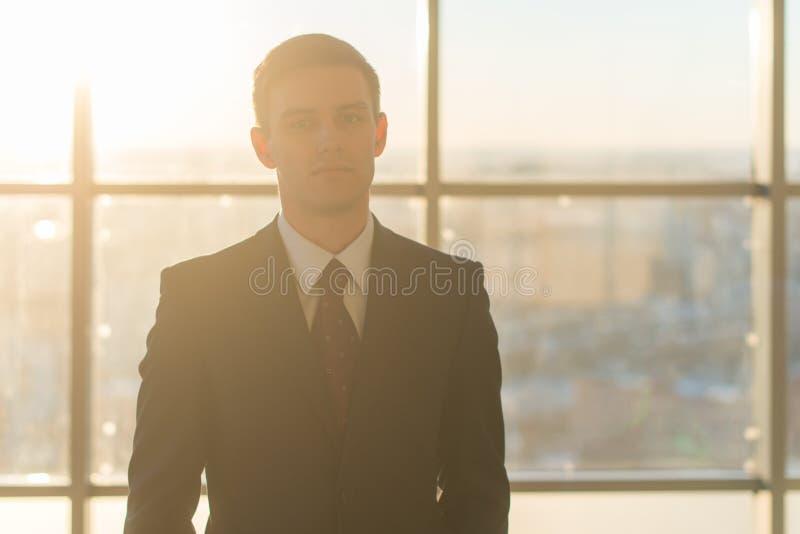 Close-upportret van een jonge knappe zakenman, die ernstig camera bekijken, die zich in licht bureau over groot bevinden royalty-vrije stock foto