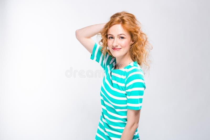 Close-upportret van een jonge, mooie vrouw met rood krullend haar in een de zomerkleding met stroken van blauw in de studio op gr stock foto